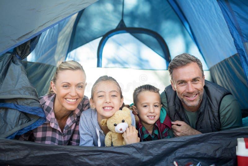 Усмехаясь семья лежа в шатре стоковые изображения rf