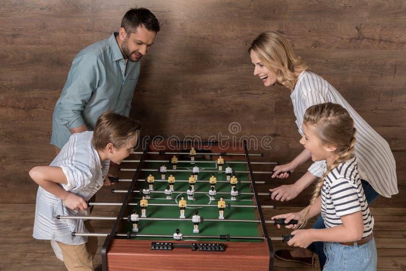 Усмехаясь семья играя foosball совместно стоковая фотография rf