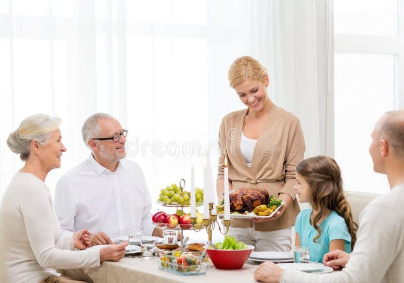 Усмехаясь семья имея обедающий праздника дома стоковое изображение rf