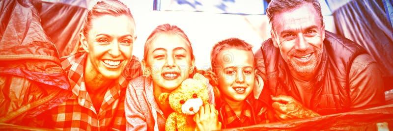 Усмехаясь семья лежа в шатре стоковые фото