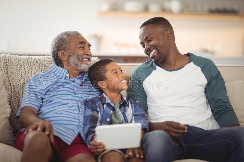 Усмехаясь семья мульти-поколения сидя совместно на софе стоковые фотографии rf