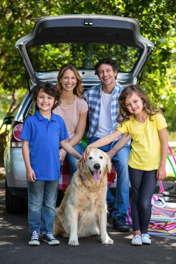 Усмехаясь семья перед автомобилем стоковая фотография rf