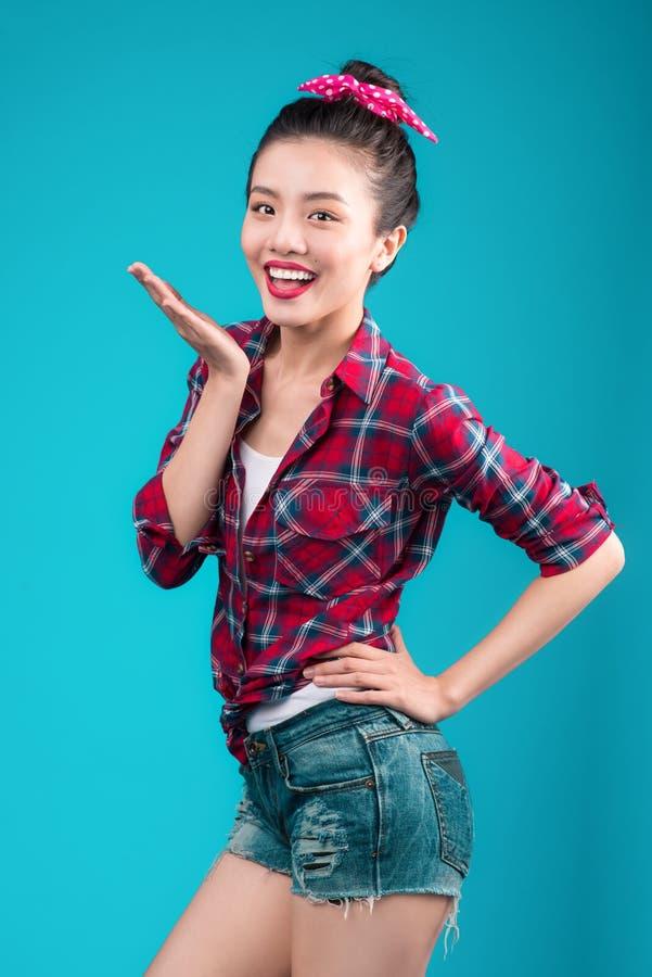 Усмехаясь симпатичная азиатская женщина одела в платье стиля штыря-вверх над bl стоковые изображения rf