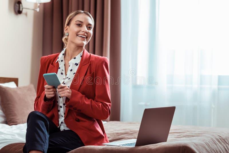 Усмехаясь симпатичная дама в красной куртке сидя на кровати стоковое изображение rf