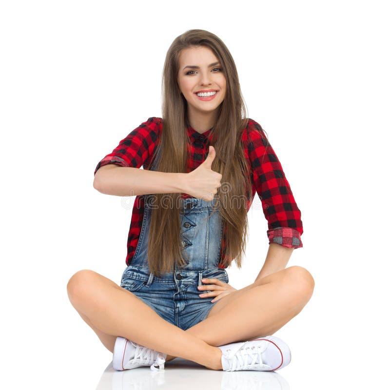 Усмехаясь сидя большие пальцы руки женщины вверх стоковое изображение