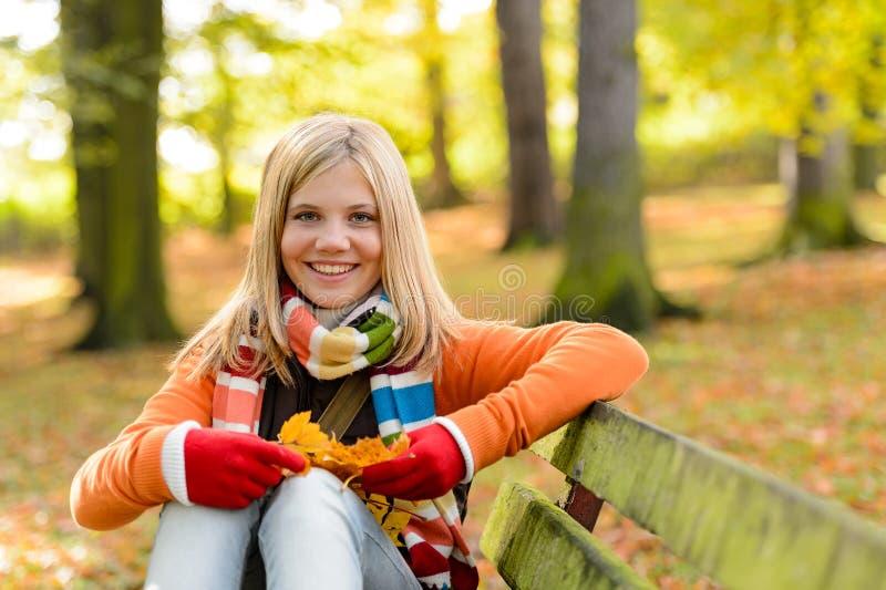 Усмехаясь скамейка в парке осени девушки подростка сидя стоковые изображения rf