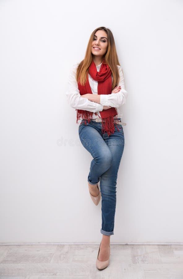 Усмехаясь склонность женщины на стене стоковая фотография rf