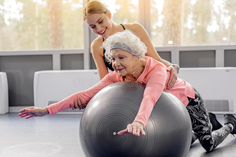 Усмехаясь склонность пенсионера на fitball стоковое фото rf