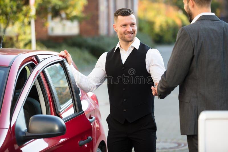 Усмехаясь слуга и предприниматель стоя близко автомобиль стоковая фотография