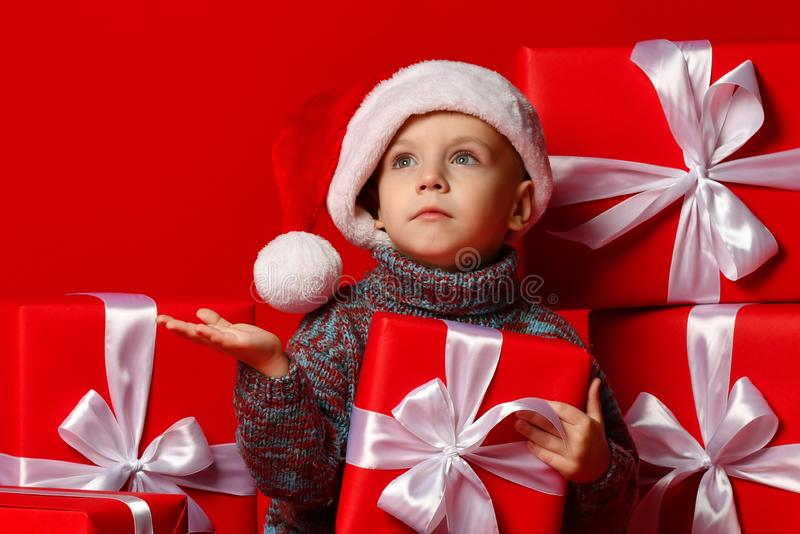 Усмехаясь смешной ребенок в шляпе Санты красной держа подарок рождества в руке Принципиальная схема рождества стоковое фото