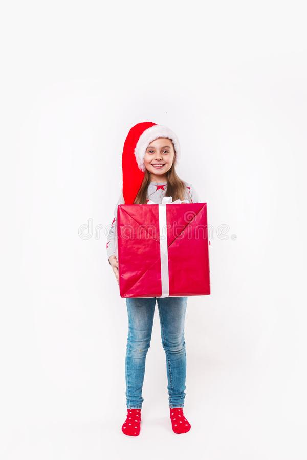 Усмехаясь смешной ребенок в шляпе Санты красной держа подарок рождества в руке Принципиальная схема рождества стоковые фотографии rf