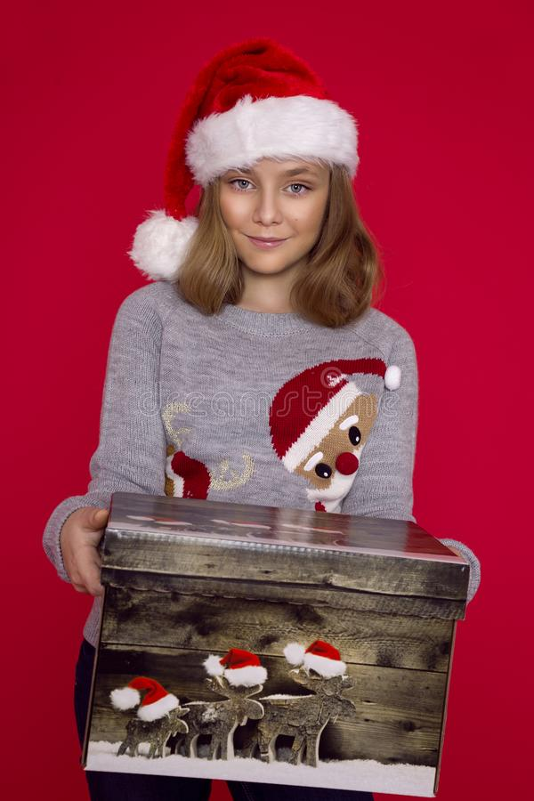Усмехаясь смешной ребенок в шляпе Санты красной держа подарок рождества в руке Принципиальная схема рождества стоковое изображение