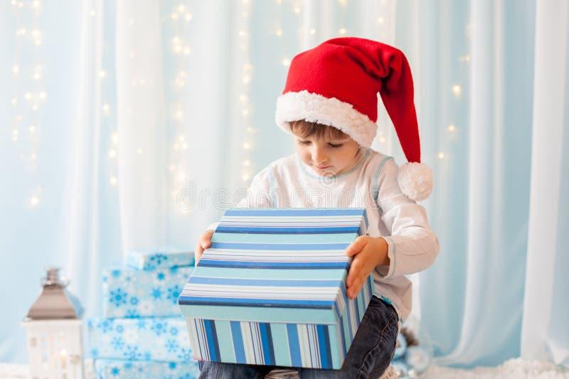 Усмехаясь смешной ребенок в шляпе Санты красной держа подарок рождества в h стоковые фото