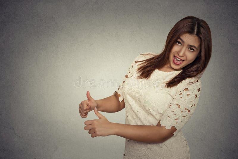 Усмехаясь смеясь над женщина стоя дающ большой палец руки вверх стоковые фото