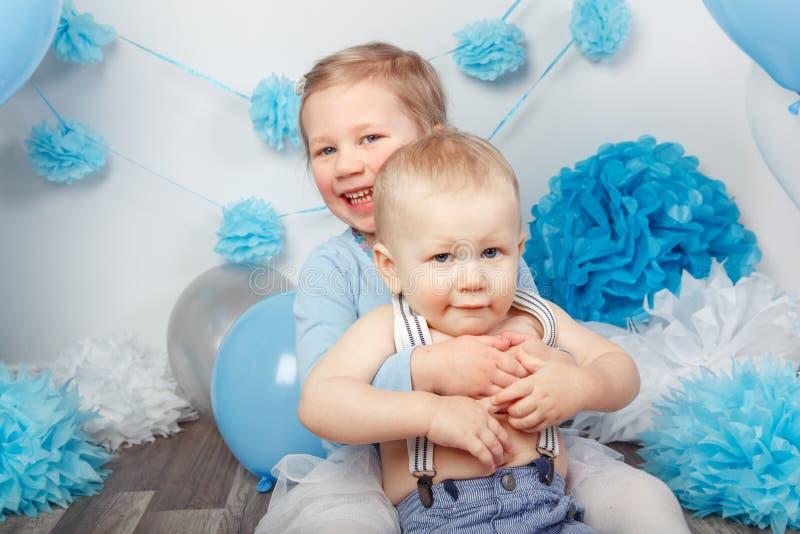 2 усмехаясь смеясь над обнимая милых прелестных кавказских дет, девушка малыша и ребёнок, празднуя день рождения стоковое фото rf