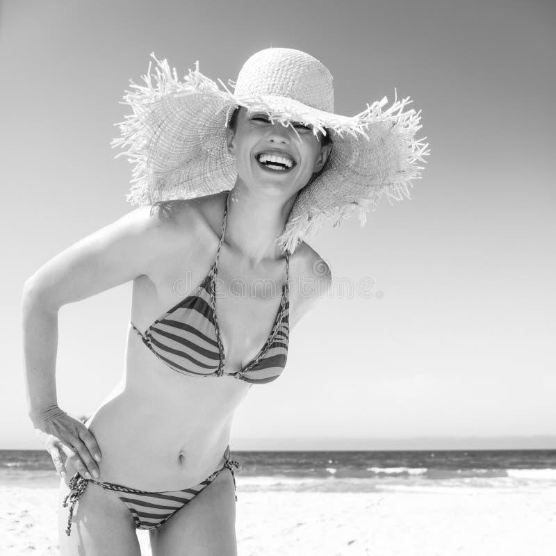 Усмехаясь современная женщина в соломенной шляпе бикини и пляжа на береге моря стоковая фотография rf