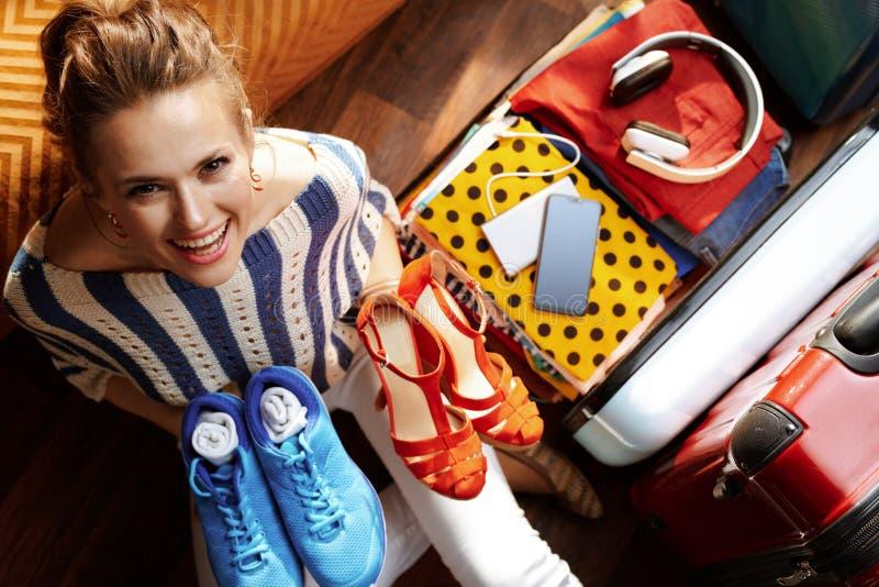 Усмехаясь современная женщина пакуя блестящие и удобные ботинки стоковые фотографии rf