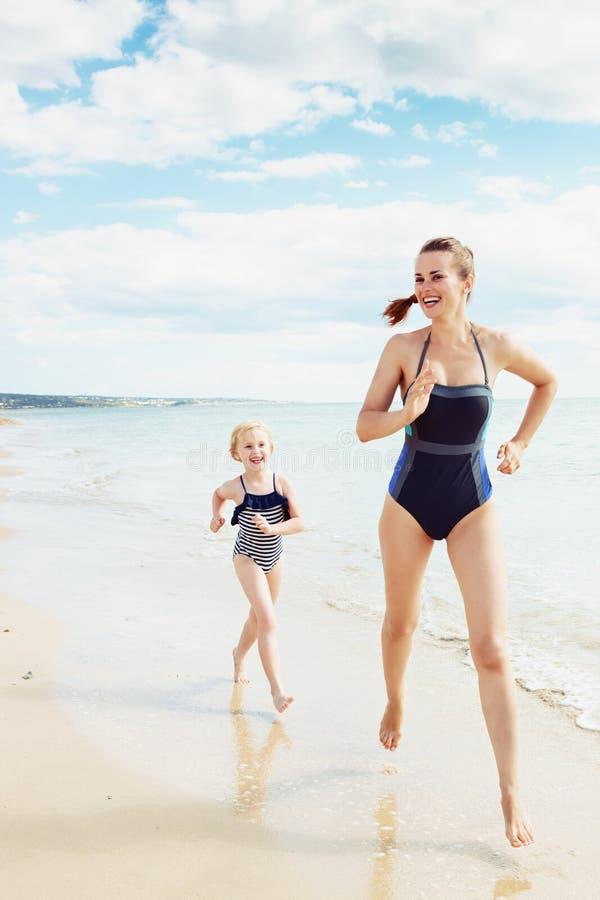 Усмехаясь современные мать и ребенок в купальнике на ходе пляжа стоковые изображения rf