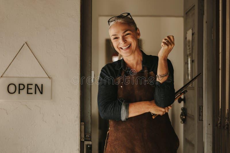 Усмехаясь создатель ювелирных изделий на входе мастерской стоковые фото