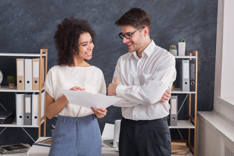 Усмехаясь сотрудники говоря и обсуждая документ в офисе стоковое фото rf