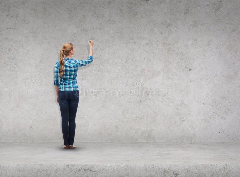 Усмехаясь сочинительство молодой женщины на виртуальном экране стоковая фотография