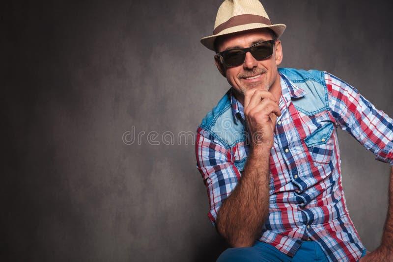Усмехаясь солнечные очки старшего вскользь человека нося и шляпа лета стоковые изображения