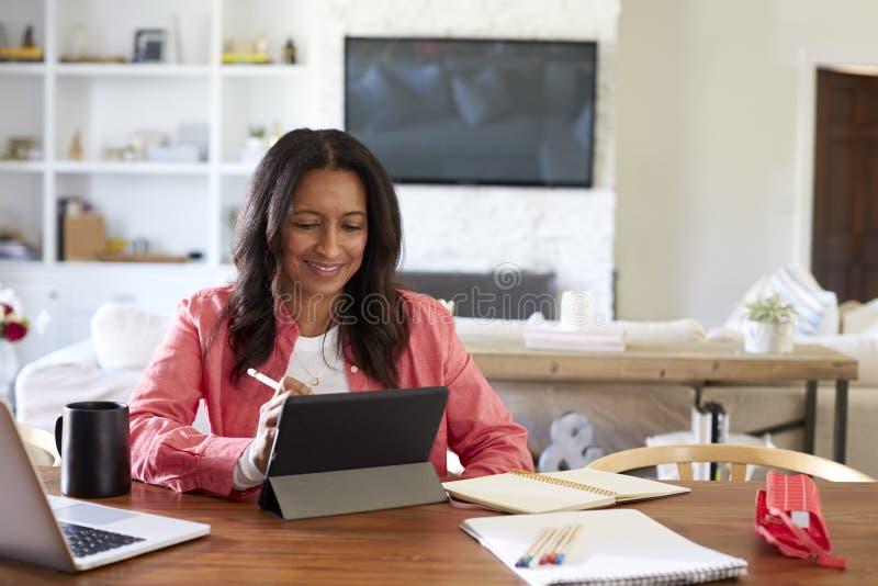 Усмехаясь средняя достигшая возраста женщина сидя на чертеже таблицы на планшете с грифелем, вид спереди стоковая фотография rf