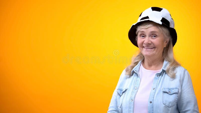 Усмехаясь старуха нося смешную шляпу футбола, шаблон для объявления, д стоковая фотография rf