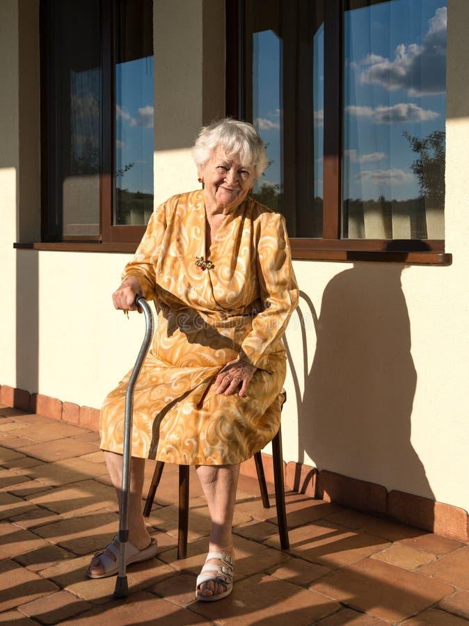 Download Усмехаясь старуха сидя около дома Стоковое Фото - изображение насчитывающей бабушка, outdoors: 41659432