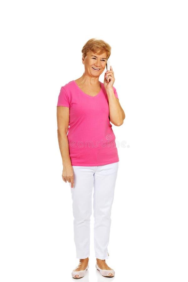 Усмехаясь старшая женщина говоря через телефон стоковое изображение