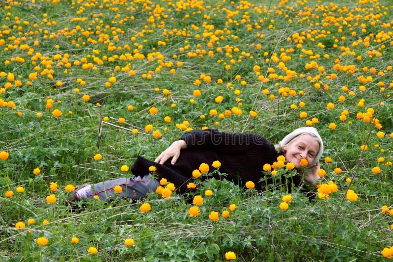 Усмехаясь старшая женщина на цветках поля стоковая фотография