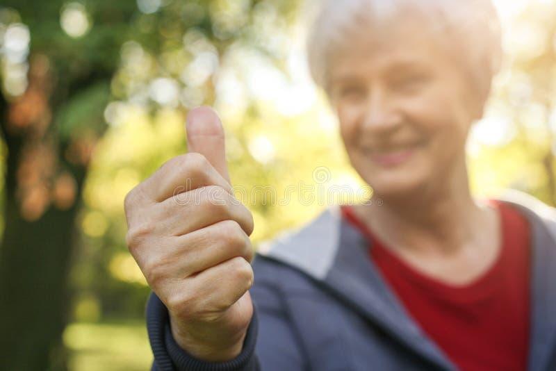Усмехаясь старшая женщина показывая О'КЕЫ стоковое изображение