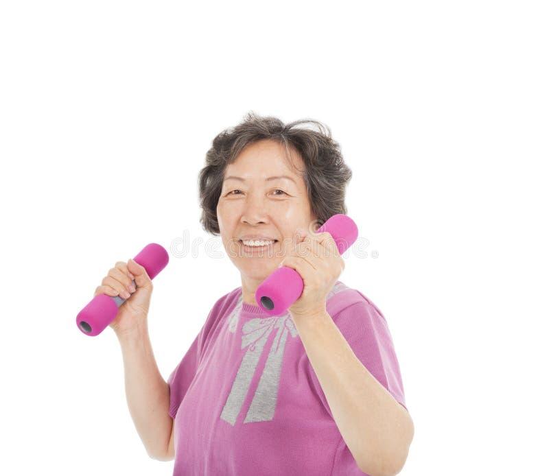 Усмехаясь старшая женщина разрабатывая с гантелями стоковое фото rf