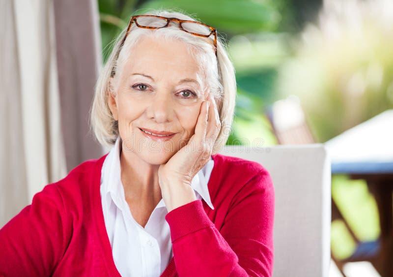 Усмехаясь старшая женщина сидя на доме престарелых стоковые фотографии rf