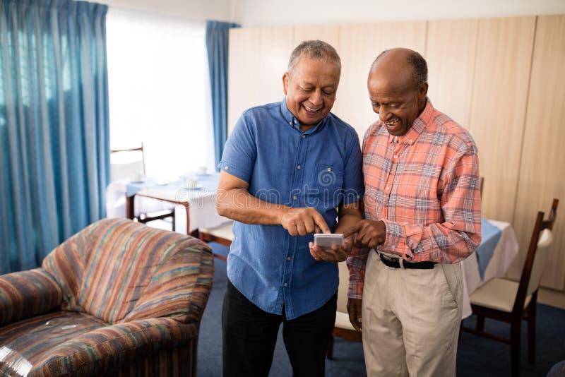Усмехаясь старшие мужские друзья используя мобильный телефон стоковое фото rf