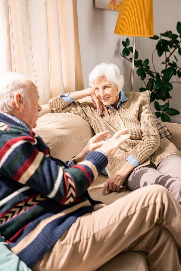 Усмехаясь старшие пары беседуя дома стоковая фотография