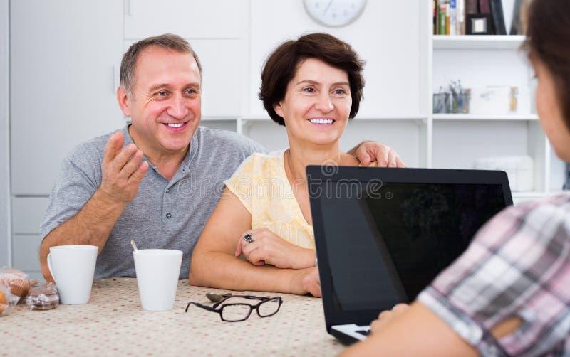 Усмехаясь старшие пары слушая к молодой женщине стоковое изображение rf