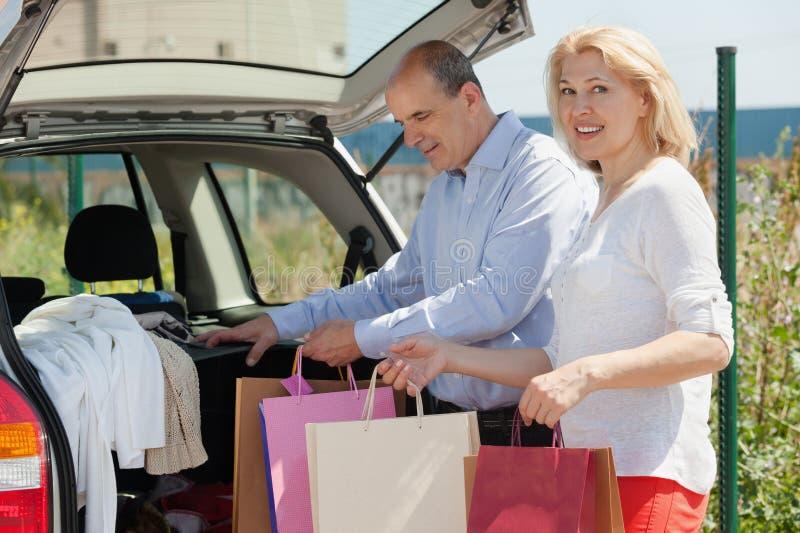 Усмехаясь старшие супруги с сумками стоковые изображения rf