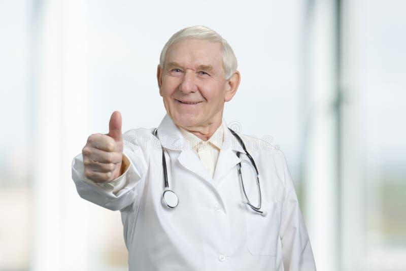 Усмехаясь старший доктор с большим пальцем руки вверх стоковое фото rf