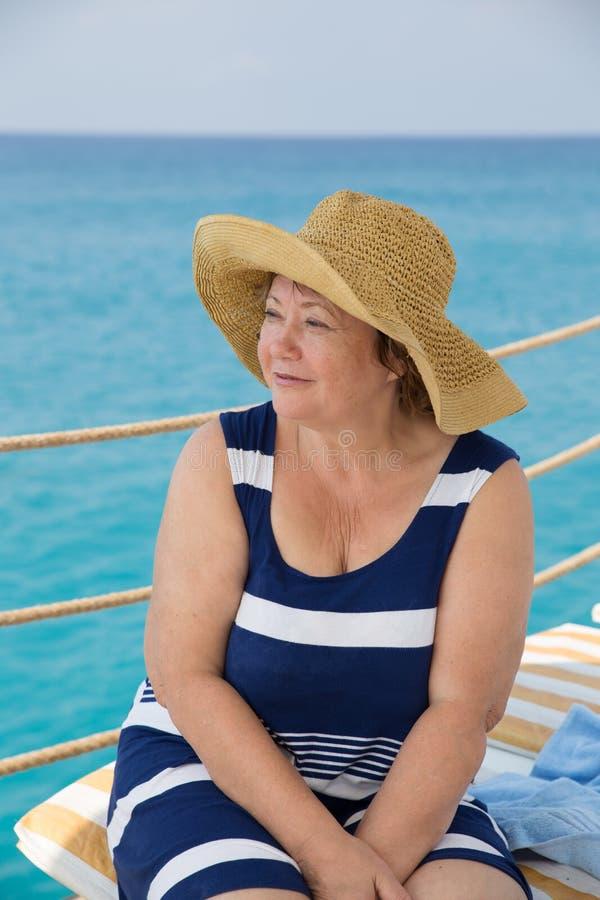 Усмехаясь старший пляж женщины на море lokking прочь стоковое изображение rf