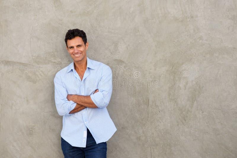 Усмехаясь стена красивого человека среднего возраста готовя стоковое фото