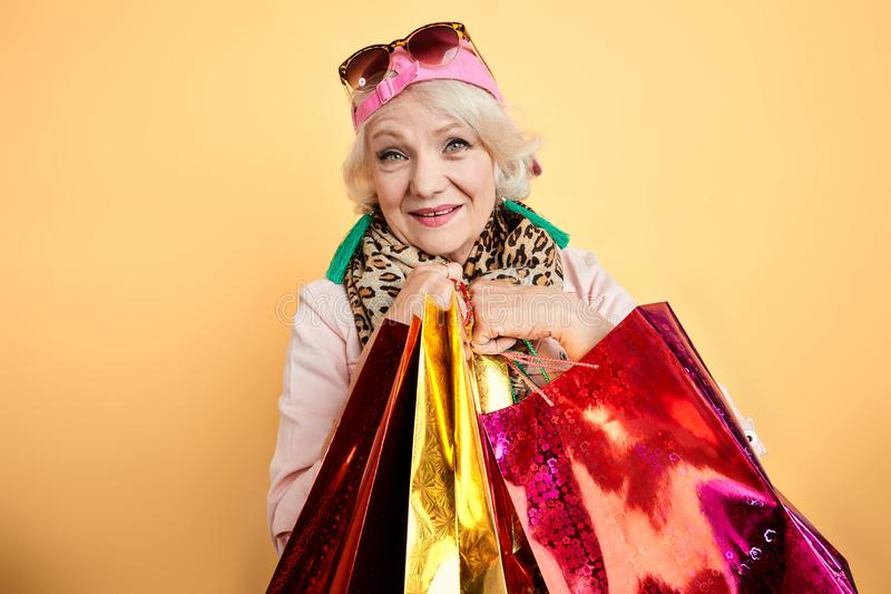 Усмехаясь стильная пожилая женщина делая покупки стоковые изображения