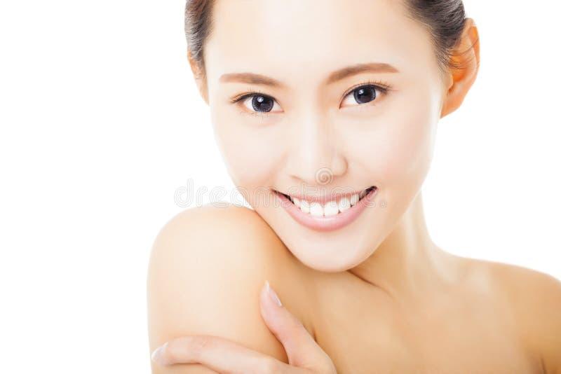 усмехаясь сторона молодой женщины изолированная на белизне стоковое фото rf