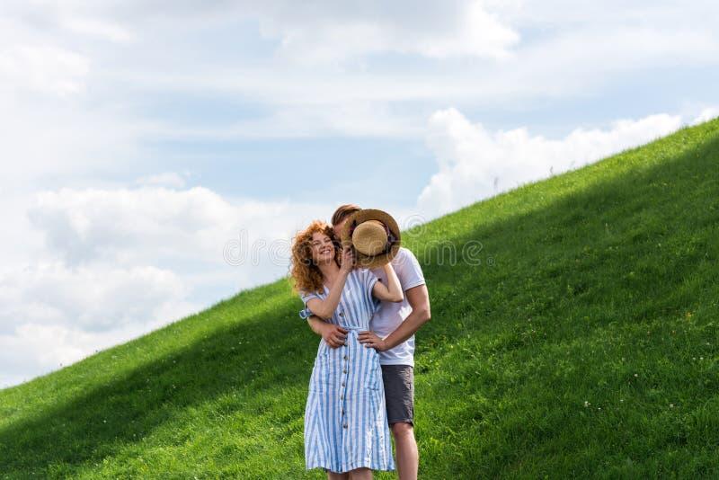 усмехаясь сторона парня заволакивания женщины redhead соломенной шляпой на травянистом стоковые фото