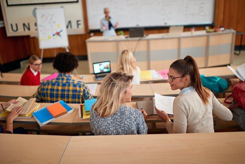 Усмехаясь студенты слушая лектор в амфитеатре стоковое изображение