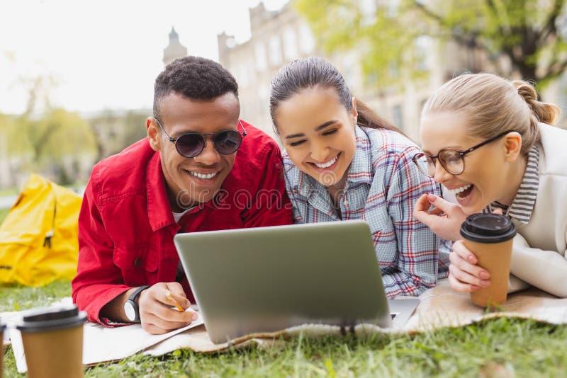 Усмехаясь студент-выпускники наблюдая комедию в парке стоковые фото