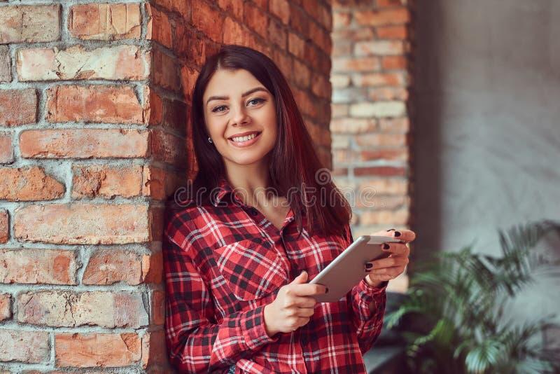 Усмехаясь студент девушки брюнет одел в рубашке и джинсах шотландки держа цифровую таблетку пока полагающся на кирпичной стене вн стоковые изображения