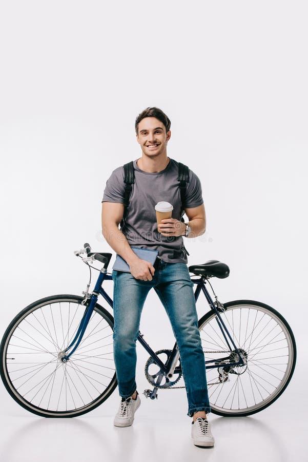 усмехаясь студент держа кофе для того чтобы пойти и полагаясь на велосипеде стоковая фотография rf