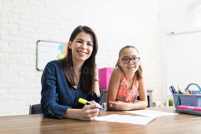 Усмехаясь студент порции учителя с Schoolwork дома стоковая фотография rf