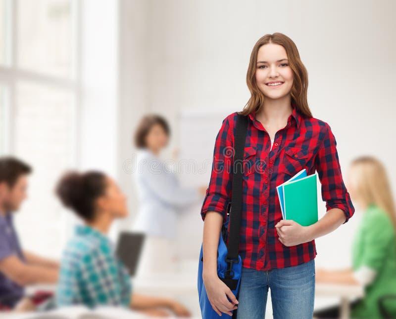 Усмехаясь студентка с сумкой и тетрадями стоковая фотография